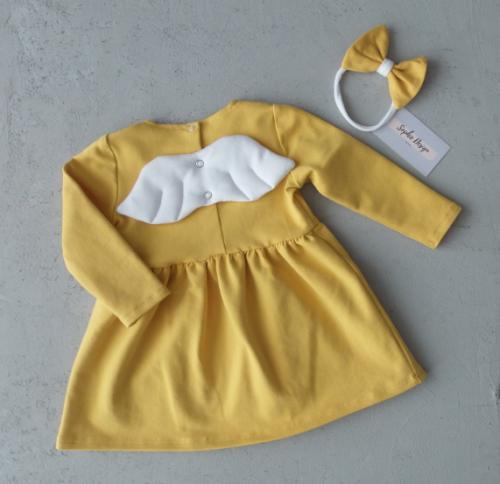 Sukienka musztardowa z białymi skrzydełkami.
