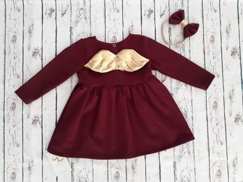 Bordowa sukienka dla dziewczynki ze złotymi skrzydłami.